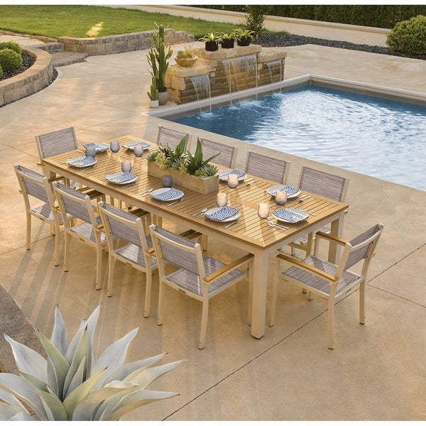 Oxford Garden Travira 11-piece 103-in x 42-in Tekwood Natural Table & Sling Armchair Dining Set - Bellows Sling. Opens flyout.