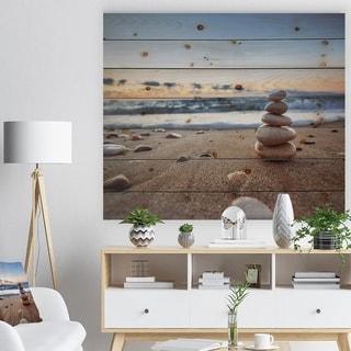 Designart 'Stones Balance on Sandy Beach' Seashore Print on Natural Pine Wood - Brown