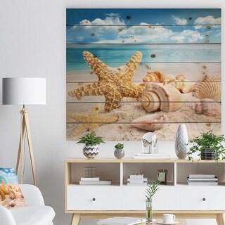 Designart 'Starfish and Seashells on Beach' Seashore Photo Print on Natural Pine Wood - Multi-color