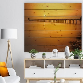 Designart 'Yellow Tinged Seashore and Long Pier' Pier Seascape Print on Natural Pine Wood - Orange