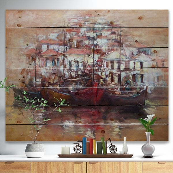 Designart 'Four Boats At Pier Near Village' Sea & Shore Painting Print on Natural Pine Wood - Brown