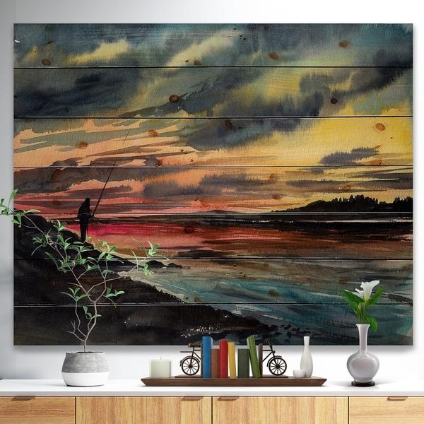 Designart 'Fishing Man over Sunset Sky' Landscapes Painting Print on Natural Pine Wood - Blue