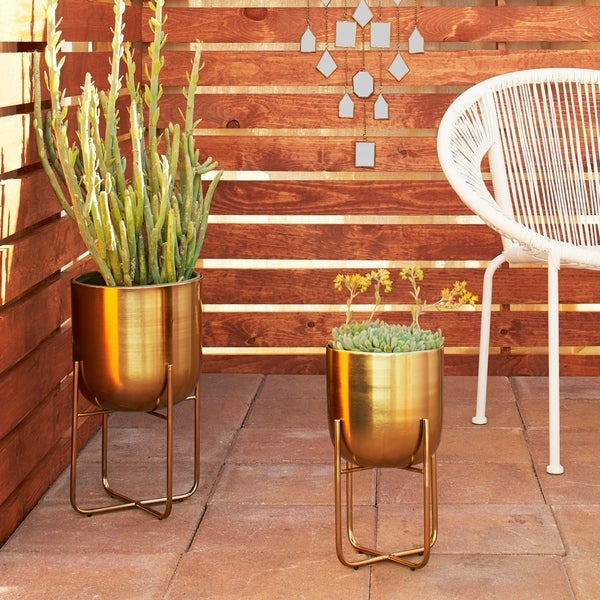 """Studio 350 Contemporary Style Round Indoor/Outdoor Metallic Gold Metal Planters in Gold Stands, Set of 2: 10"""" x 16"""", 8"""" x 13"""". Opens flyout."""
