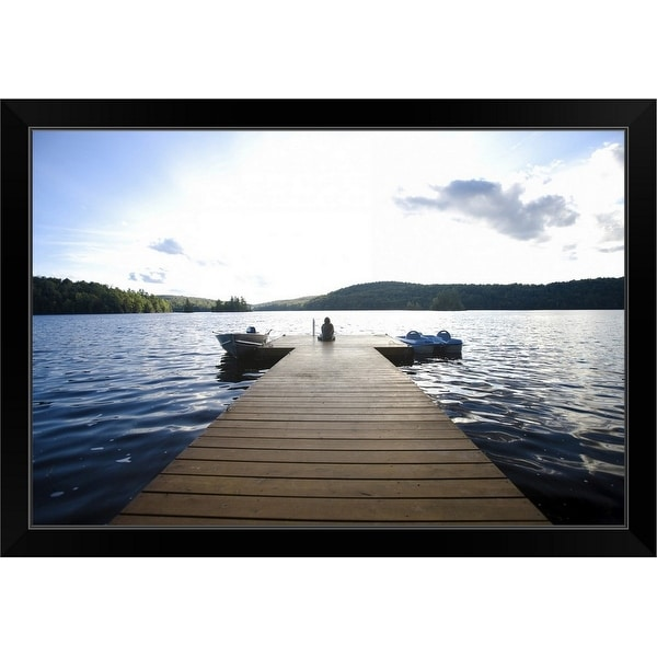 """Person sitting on dock with two boats in water"" Black Framed Print"