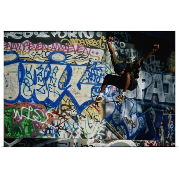 Poster Print entitled Male skateboarder in mid-air, graffiti-covered wall in background - multi-color