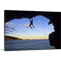 Premium Thick-Wrap Canvas entitled Silhouette of man rock climbing in cave over water - Multi-color