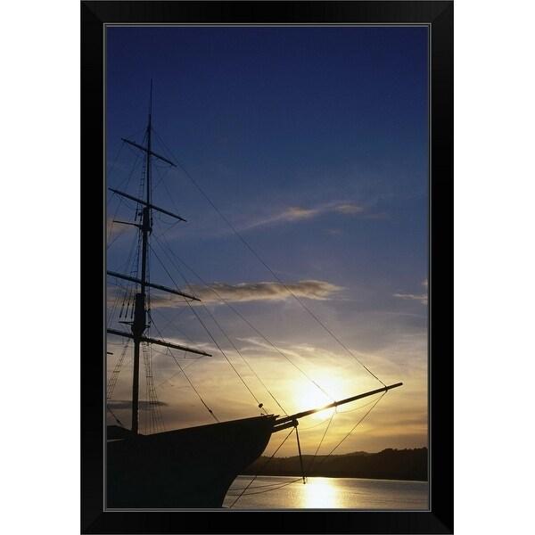 """A setting sun silhouettes an old sailing ship"" Black Framed Print"