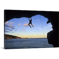 Premium Thick-Wrap Canvas entitled Silhouette of man rock climbing in cave over water