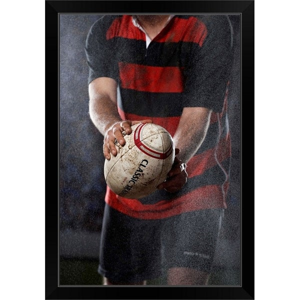 """""""Rugby player holding ball in rain, mid section"""" Black Framed Print"""