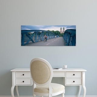 Easy Art Prints Panoramic Images's 'Woman riding a bicycle on a bridge with a church in the background, Herz