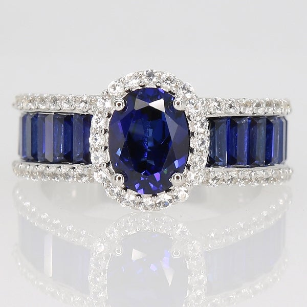 Oval & Baguette-cut Created Blue and White Sapphire Halo Engagement Ring in Sterling Silver by Miadora. Opens flyout.