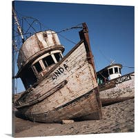 Premium Thick-Wrap Canvas entitled old neglected boats sit beached on sand under a blue sky