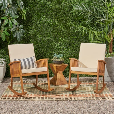 Two wooden beige rocking chairs on outdoor area rug on sale and up to 25% off online at Overstock.com