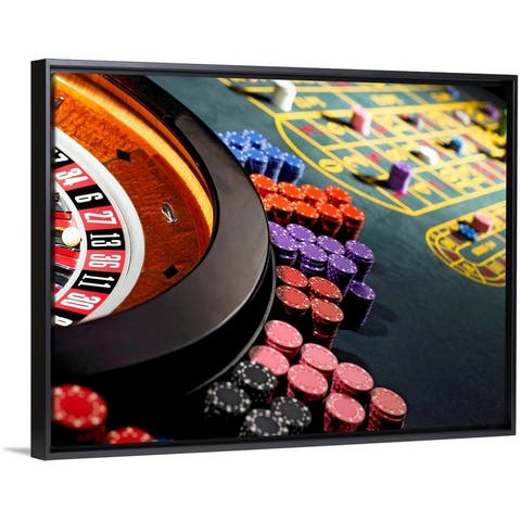 """""""Gambling chips stacked around roulette wheel on gaming table"""" Black Float Frame Canvas Art"""