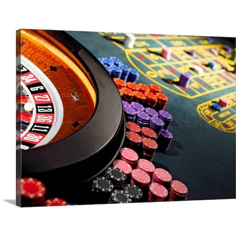 """Gambling chips stacked around roulette wheel on gaming table"" Canvas Wall Art"