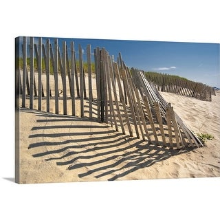 """""""The low sun casts long shadows of a wooden fence on a sandy dune by the ocean."""" Canvas Wall Art"""