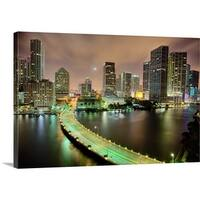 Premium Thick-Wrap Canvas entitled Bridge leads across waterway to downtown Miami sklyine at night. - Multi-color