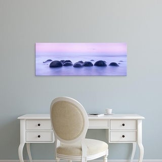 Easy Art Prints Panoramic Images's 'Boulders on the beach at sunrise, South Island, New Zealand' Premium Canvas Art