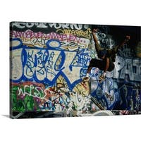 Premium Thick-Wrap Canvas entitled Male skateboarder in mid-air, graffiti-covered wall in background