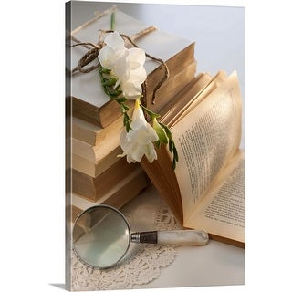 """""""Magnifying glass beside stack of books with flowers"""" Canvas Wall Art"""