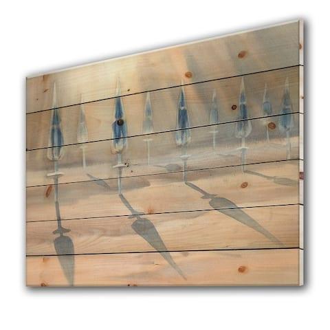Designart 'Sunny Sand With Closed Blue Beach Umbrellas' Lake House Print on Natural Pine Wood
