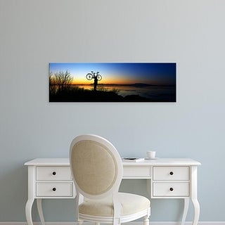 Easy Art Prints Panoramic Image 'Cyclist holding bicycle over head, river's edge, sunset, Alaska.' Canvas Art