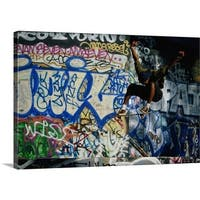 Premium Thick-Wrap Canvas entitled Male skateboarder in mid-air, graffiti-covered wall in background - Multi-color