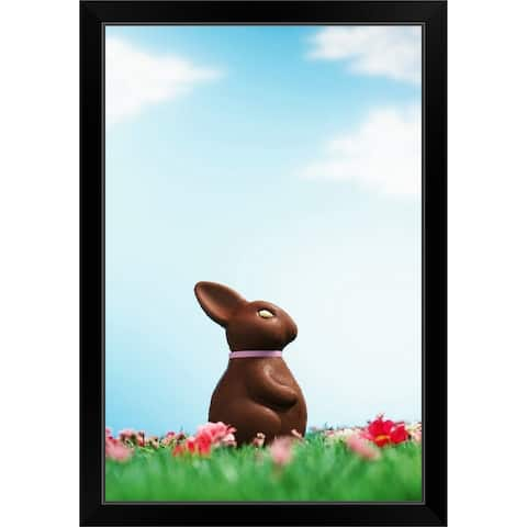 """""""Chocolate Easter bunny amongst flowers in grass, side view"""" Black Framed Print"""
