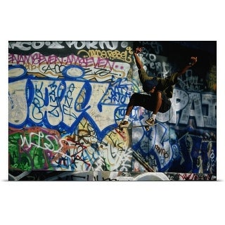 Poster Print entitled Male skateboarder in mid-air, graffiti-covered wall in background