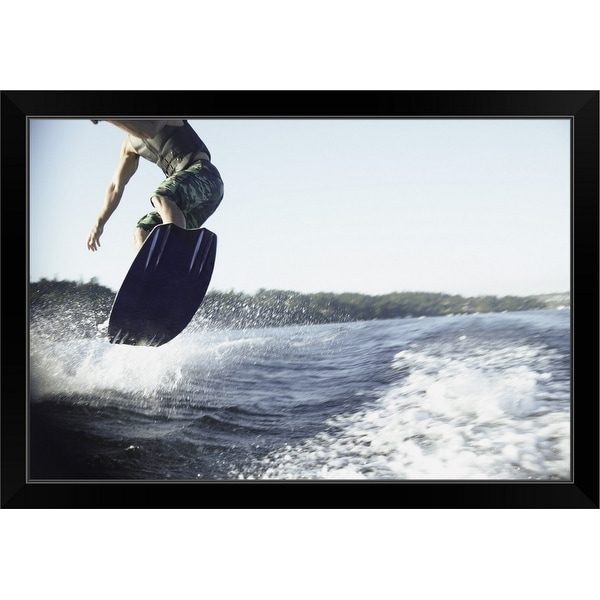 """Man wake boarding"" Black Framed Print"