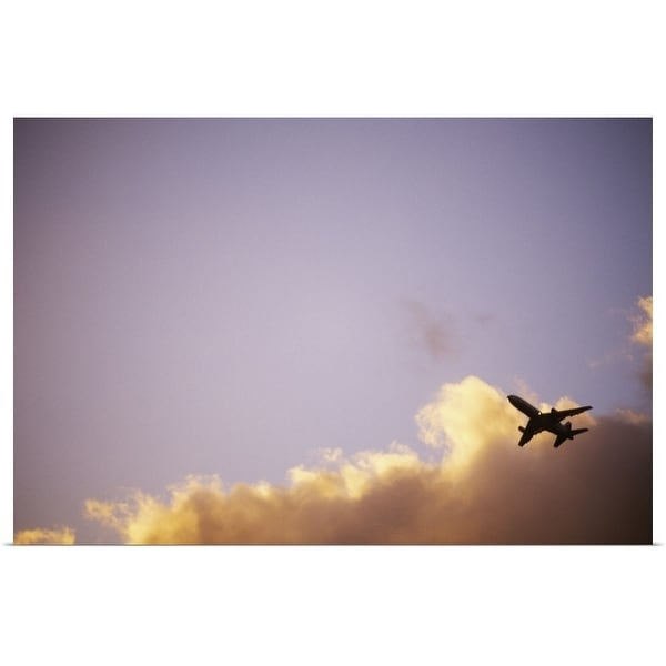 """Airplane soars through blue sky and clouds at sunset."" Poster Print"
