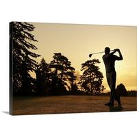 Premium Thick-Wrap Canvas entitled Golfer swinging club on golf course at sunset - Multi-color