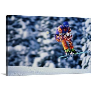 """Skiing, Downhill event, competitor jumping over ridge, trees behind"" Canvas Wall Art"