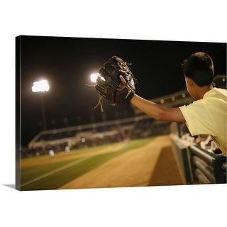 """Kid leaning over wall to try and catch 'foul 'ball at nighttime baseball game"" Canvas Wall Art"