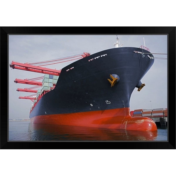 """Bow view of a cargo ship being loaded at port."" Black Framed Print"