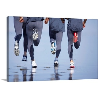 """""""Four men jogging on beach, low section, rear view"""" Canvas Wall Art"""