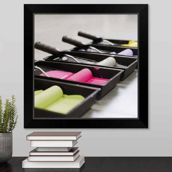 """""""Close-up side view of trays of coloured paint and paint rollers"""" Black Framed Print"""
