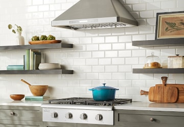 Stainless steel range hood in a modern farmhouse kitchen