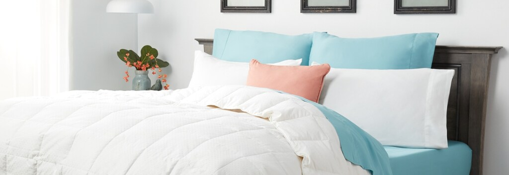 White down comforter with blue sheets in beautiful bedframe