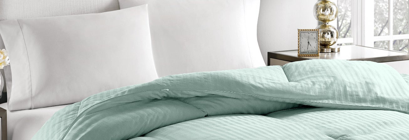 Bed with turquoise comforter and white sheets