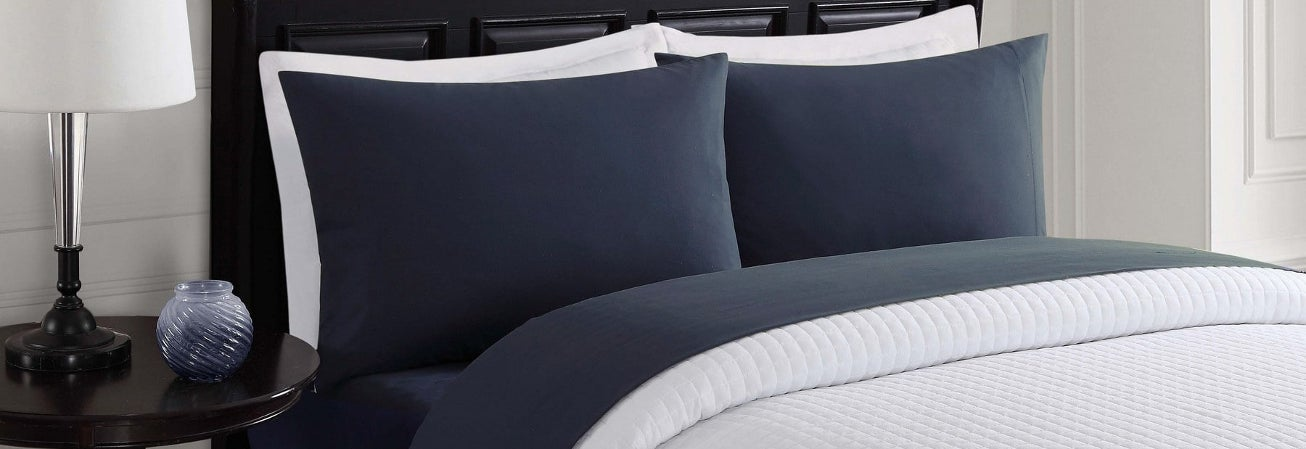 Blue sheets and pillow cases with white bedspread