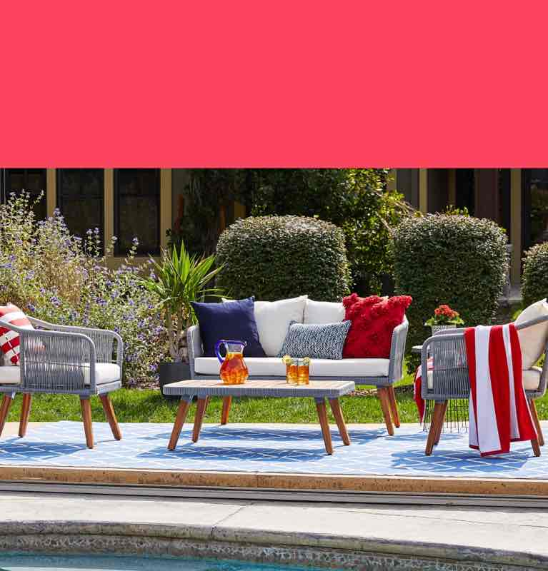 Outdoor patio furniture set with white cushions and decorative throw pillows on a blue area rug