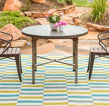 Outdoor patio table with two chairs and multi-colored outdoor rug.
