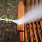 A hose, power washing a teak outdoor chair.