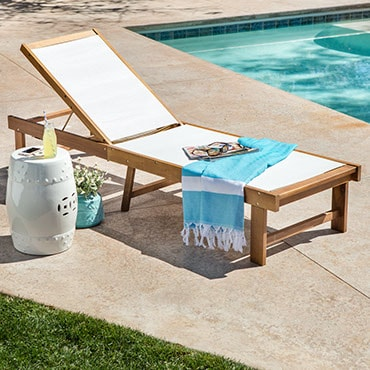 An acacia and white canvas chaise lounge, poolside, with side table and Turkish towel