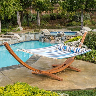 A striped, canvas hammock on a hammock stand, poolside