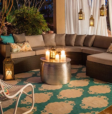 An evening shot of an all-weather wicker conversation set with candles, lanterns, and a teal outdoor rug