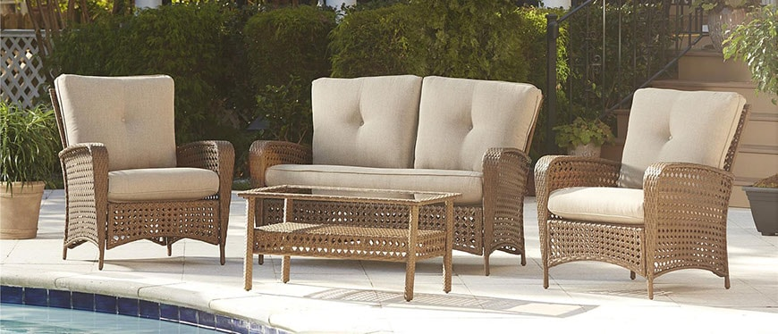 An all-weather wicker conversation set with natural outdoor cushions
