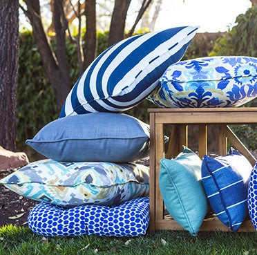 A collection of outdoor cushions and pillows in blue tones