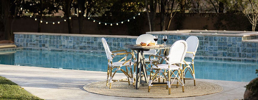 An outdoor dining set, poolside, with a jute rug